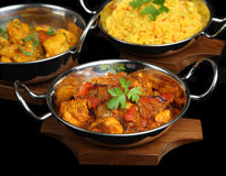 Indian Curry Meal. Indian chicken jalfrezi with Bombay aloo potato curry isolated on black Royalty Free Stock Photo