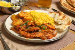Indian Curry Meal. Indian chicken jalfrezi with Bombay aloo (potato curry), pilau rice and naan bread Stock Image