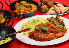 Indian Curry Meal. Chicken Jalfrezi with saag aloo vegetable curry and pliau rice, pakoras and samosas Royalty Free Stock Photos