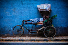 Indian cycle rickshaw driver sleeps on his bicycle in street of New Delhi, India