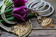 Indian decorations for dancing: bracelets, necklace. Purple ultraviolet tulips on old rustic wooden background stock photo