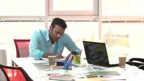 Indian designer working hard in office. Designer tired of work, huge bright windows background stock video footage