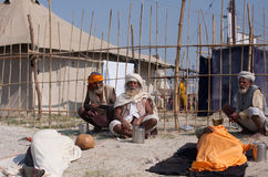 Indian devotees rest near the holy Sangam Stock Photos
