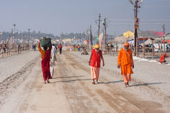 Indian devotees walking to holy Sangam Stock Photos