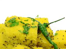 Indian dhokla on white background. Indian dhokla with green chilly and green coriander. useful in food items Royalty Free Stock Photography
