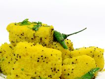 Indian dhokla on white background. Indian dhokla with green chilly and green coriander. useful in food items Stock Photography