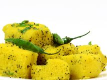 Indian dhokla on white background. Indian dhokla with green chilly and green coriander. useful in food items Stock Photo