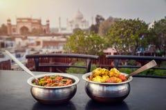 Indian dinner near Taj Mahal. Aloo Gobi and Sabji Masala Traditional Indian food in metal plates on rooftop restaurant with Taj Mahal view in Agra, Uttar Pradesh Stock Image