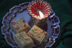Indian Diwali sweet barfi with a burning lamp. Indian Diwali sweet barfi with burning lamp Stock Image