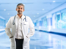 Indian doctor. Mature Indian male medical doctor standing inside hospital. Handsome Indian model portrait royalty free stock image