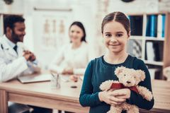 Indian doctor seeing patients in office. Daughter is posing with teddy bear. stock image