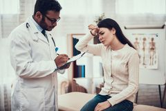 Indian doctor seeing patients in office. Doctor is listening to woman`s symptoms. Woman has high temperature. Indian doctor in white gown seeing patients in stock photos