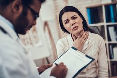 Indian doctor seeing patients in office. Doctor is listening to woman`s symptoms. Woman has sore throat. Indian doctor in white gown seeing patients in office stock photo