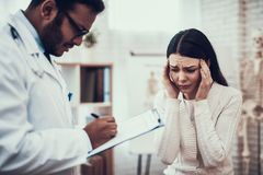 Indian doctor seeing patients in office. Doctor is listening to woman`s symptoms. Woman`s head hurts. Indian doctor in white gown seeing patients in office royalty free stock photo