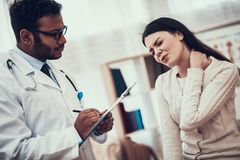 Indian doctor seeing patients in office. Doctor is listening to woman`s symptoms. Woman`s neck hurts. Indian doctor in white gown seeing patients in office royalty free stock photo