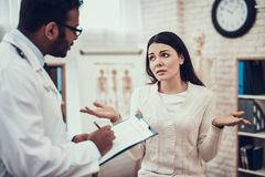 Indian doctor seeing patients in office. Doctor is listening to woman`s symptoms. Indian doctor in white gown seeing patients in office. Doctor is listening to stock images