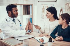 Indian doctor seeing patients in office. Mother is giving money to doctor. Doctor is refusing. royalty free stock photo