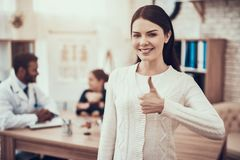 Indian doctor seeing patients in office. Mother is posing giving thumbs up. Indian doctor in white gown seeing patients in office. Mother is posing giving royalty free stock photo