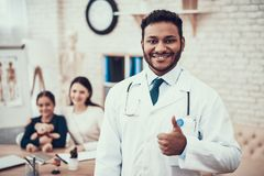Indian doctor seeing patients in office. Doctor is posing giving thumbs up. Indian doctor in white gown seeing patients in office. Doctor is posing giving stock photography
