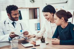 Indian doctor seeing patients in office. Doctor is showing clipboard to mother and daughter. stock photo