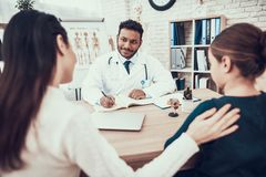 Indian doctor seeing patients in office. Doctor is taking notes listening to mother and daughter. royalty free stock image