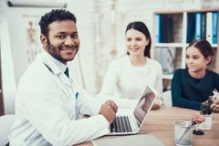 Indian doctor seeing patients in office. Doctor is talking to mother and daughter using laptop. royalty free stock photo