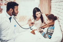 Indian doctor seeing patients at home. Doctor is using stethoscope. Pregnant mother and daughter. stock images