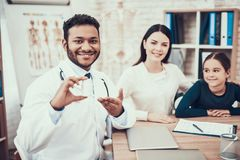 Indian doctor seeing patients in office. Doctor is giving mother and daughter bottle of pills. stock photo