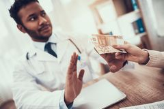 Indian doctor seeing patients in office. Mother is giving money to doctor. Doctor is refusing. stock photography