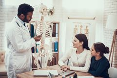 Indian doctor seeing patients in office. Doctor is showing skeleton to mother and daughter. royalty free stock photography