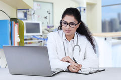 Indian doctor working in the clinic. Portrait of young doctor working in the hospital while looking at laptop and write on clipboard Stock Images