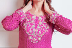 Indian designer dress. Pattern of a pinkish purple Indian desinger dress with beautiful flowery designs Stock Photo