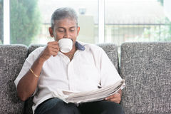 Indian drinking coffee and reading newspaper Royalty Free Stock Photo