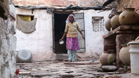 Indian elder woman walking slowly in the front yard of her home. stock video footage