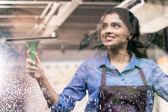 Indian employee cleaning windows. With squeegee Royalty Free Stock Photos