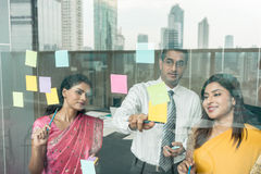 Indian employees sticking reminders on glass wall in the office Stock Photography