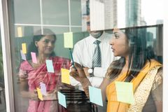 Indian employees sticking reminders on glass wall in the office. Three Indian employees sticking reminders on glass wall with business tasks and deadlines in the Royalty Free Stock Photo