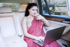 Indian entrepreneur uses laptop in car Royalty Free Stock Image