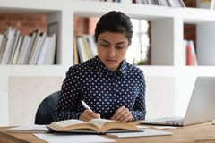 Free Indian Ethnicity Student Woman Writing Notes Reading Textbook Studying Indoors Royalty Free Stock Images - 161581289