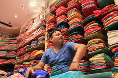 Indian Fabric Business. A traditional sales man sitting on a mattress on ground shows dresses to a  customer  traditional Jaipur designer dresses called gota Stock Images