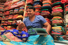 Indian Fabric Business. A traditional sales man sitting on a mattress on ground shows dresses to a customer traditional Jaipur designer dresses called gota patti royalty free stock photography