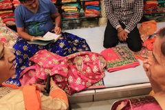 Indian Fabric Business. Indian women selecting, negotiating and buying traditional Jaipur designer dresses called gota patti, worked with motifs created with Stock Photos