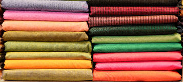 INDIAN FABRIC SAREES. Pile of colorful indian fabric sarees in the store stock image