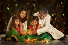 Indian family celebrating Diwali, fesitval of lights. Indian family in traditional sari lighting oil lamp and celebrating Diwali or deepavali, fesitval of lights