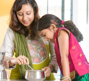 Indian family cooking at home. Asian family cooking food together at home. Indian mother and child preparing meal in kitchen. Traditional India people with sari royalty free stock photography