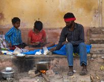 Indian family cooks porridge in pot right on street. India, Pushkar-March 3, 2018: Indian family cooks porridge in a pot right on the street of the city stock photography