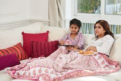Indian Family Enjoying Each Others Company. Lovely moments of motherhood: attractive Indian women covered with plaid sitting on cozy sofa next to her little Stock Photos