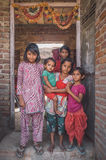 Indian family. GODWAR REGION, INDIA - 15 FEBRUARY 2015: Six girls from same family stand in doorway under decorated door arch. Post-processed with grain, texture stock photo