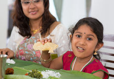Indian family having lunch. Indian family dining at home. Little girl eating snack papadum. India culture royalty free stock photo