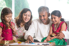 Indian family playing carrom game. Happy Asian Indian family playing carrom game at home. Parents and children indoor lifestyle Royalty Free Stock Photos